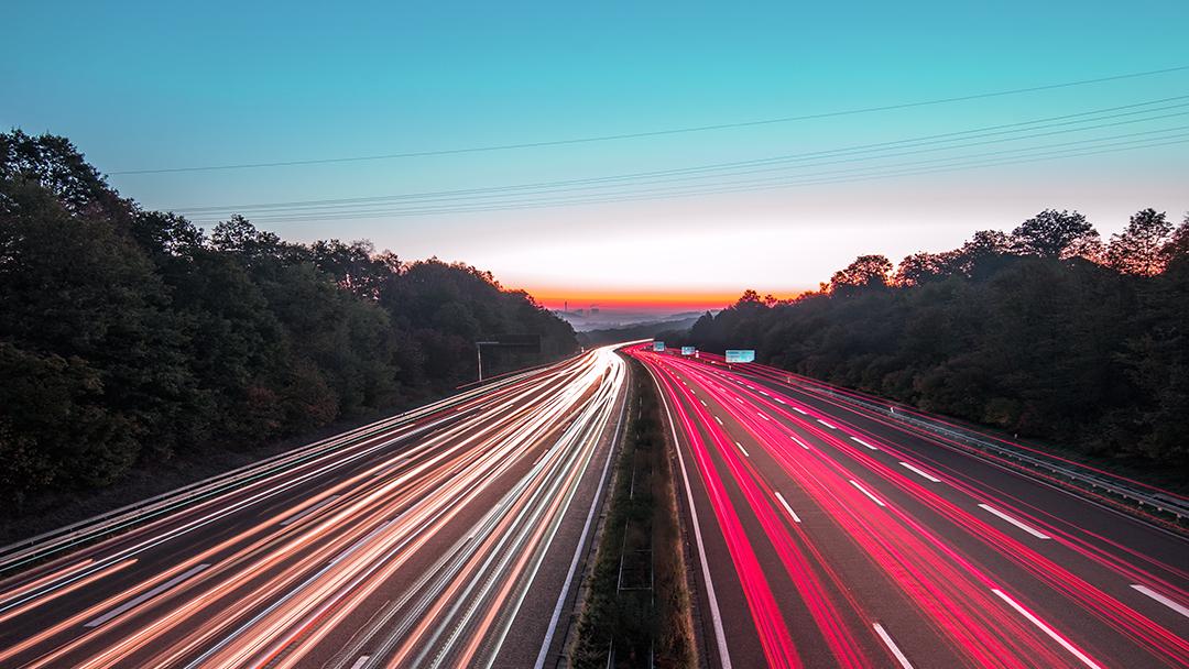 Nationale Plattform Zukunft und Mobilität Titelmotiv Autobahn im Sonnenuntergang