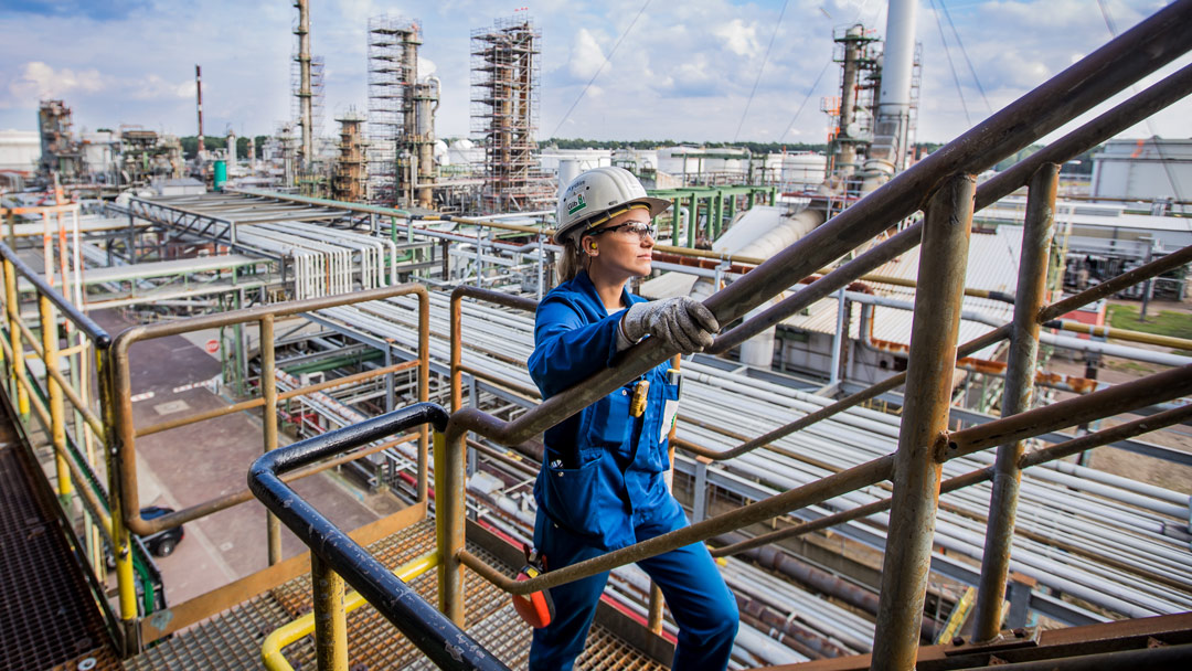 Mitarbeiterin vor BP-Raffinerie Neuausrichtung der Mineralölwirtschaft